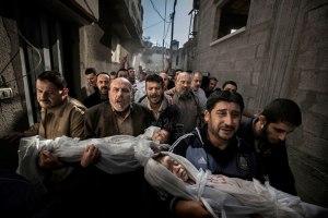 Погребение в Газа - палестински мъже носят телата на две малки деца, които са били убити по време на нападението на Газа през ноември 2012 година